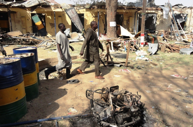 <p>Two residents pass by bombed corner shops attached to Bompai police barracks in the northern Nigerian city of Kano on Jan. 24 after multiple explosions and gun assaults by Boko Haram in the city killed at least 185 people. Boko Haram attacked Kano again today.</p>