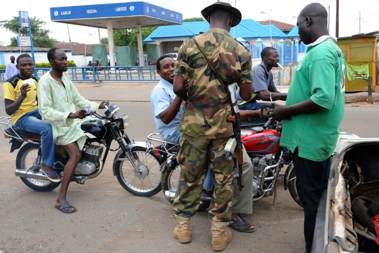 <p>Nigeria has increased its security following a number of deadly attacks by Boko Haram, a group of Islamic extremists. Here a Nigerian soldier interrogates motorcyclists at a checkpoint in Kaduna State.</p>