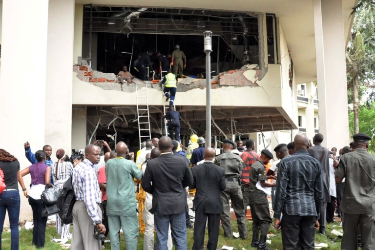 <p>Nigerians look at rescue teams working in the debris of the United Nations House in Abuja on August 26, 2011 after it was hit by a bomb that killed at least 18 people, leaving others trapped and causing heavy damage. Witnesses reported that the bomb exploded after a suspect rammed a car through the front gate. Parts of the first two floors of the building were blown out and rescue workers scrambled to rescue those left inside.</p>