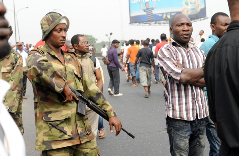 <p>A soldier stands next to protesters at Ojota district in Lagos on Jan. 16, 2012. Nigerian security forces fired tear gas and shot into the air Monday to disperse around 300 protesters in Lagos as authorities moved to prevent demonstrations in various parts of the country. Nigerian unions announced on Jan. 16 they were suspending a week-old nationwide strike over fuel prices which has shut down Africa's most populous nation and brought tens of thousands out in protest.</p>