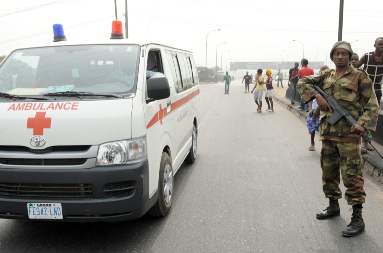 <p>An ambulance drives past a soldier standing away from protesters at Ojota district in Lagos on Jan. 16, 2012. Soldiers have been deployed in some parts of Lagos at main protest sites.</p>