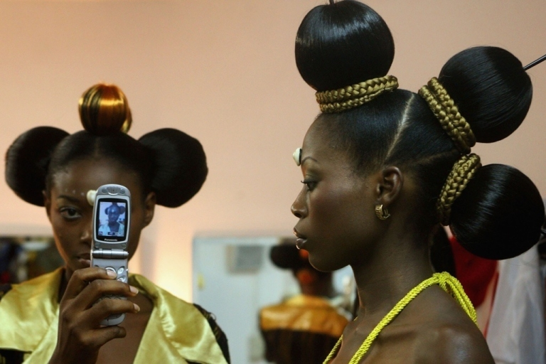 <p>Hip young Nigerians are using Twitter and other social media with their smartphones to make their elections honest and transparent. Here a Nigerian fashion models take photos of each other with a cell phone.</p>