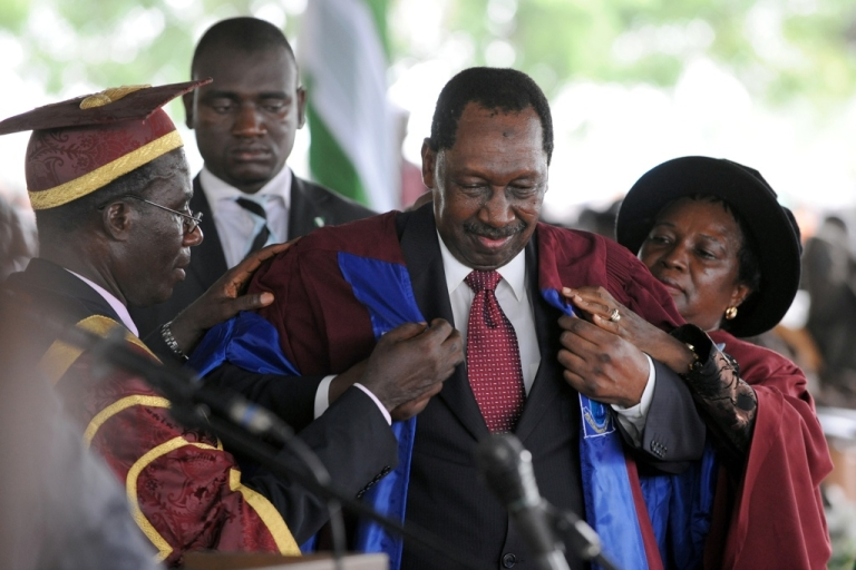 <p>Nigerian former Chief of Justice, Mohammed Uwais puts on an academic gown to earn a doctoral degree as Nigerian President Goodluck Jonathan attends graduation at his alma mater the University of Port Harcourt in Rivers State on May 15, 2010. Young Nigerians complain they must pay bribes to be admitted to Nigeria's universities.</p>