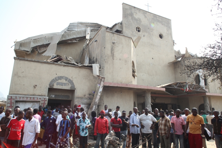 <p>People stand in front of the partially destroyed St. Theresa Catholic Church after a bomb blast in the Madala Zuba district of Nigeria's capital Abuja on December 25, 2011.  Islamist militant group Boko Haram claimed responsibility for church bombings that killed dozens of people in Nigeria that day.</p>