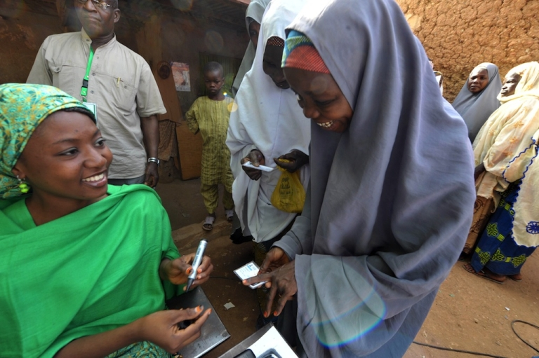 <p>An electoral worker marks the finger of a Nigerian woman at a polling station during the presidential elections in Daura on April 16, 2011.</p>