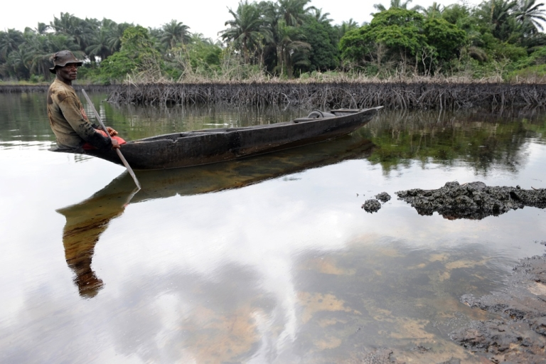 <p>Gaagaa Gidom, a 60-year-old fisherman and father of eight, looks at the spilled crude oil floating in the waters of the Niger Delta swamps of Bodo, a village in the famous Nigerian oil-producing Ogoniland, which hosts the Shell Petroleum Development Company on June 24, 2010.</p>