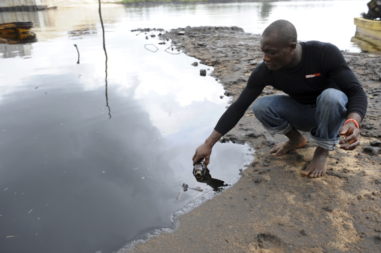 <p>A man scoops spilled crude oil into a bottle from the waters of the Niger Delta swamps of Bodo, a village in the famous Nigerian oil-producing Ogoniland, which hosts the Shell Petroleum Development Company (SPDC) in Nigeria's Rivers State. The region has in recent years experienced an average of 300 spills a year, roughly one spill a day, from terminals, pipes and platforms, according to government officials and experts. Sabotage of oil facilities by armed rebels fighting for a fairer share of oil wealth for locals, and theft of crude, popularly known as oil bunkering, in recent years saw spills spiking to new levels.</p>