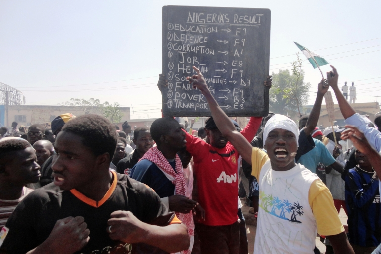 <p>A protester carries a placard against poor social services in the northern Nigerian city of Kano, on January 11, 2012. Hundreds of thousands of protesters took to the streets for a week, demonstrating against the ending of subsidy that doubled and tripled the price of fuel.</p>
