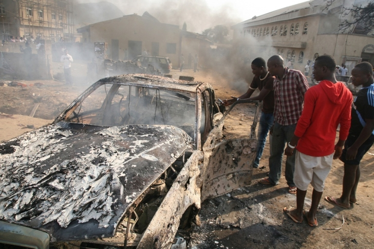 <p>Nigerians look at the wreckage of a car following a bomb blast at St Theresa Catholic Church outside the Nigerian capital Abuja on December 25, 2011. Two explosions near churches during Christmas Day services in Nigeria, including one outside the country's capital, killed at least 28 people amid spiralling violence blamed on an Islamist extremist group, Boko Haram.</p>