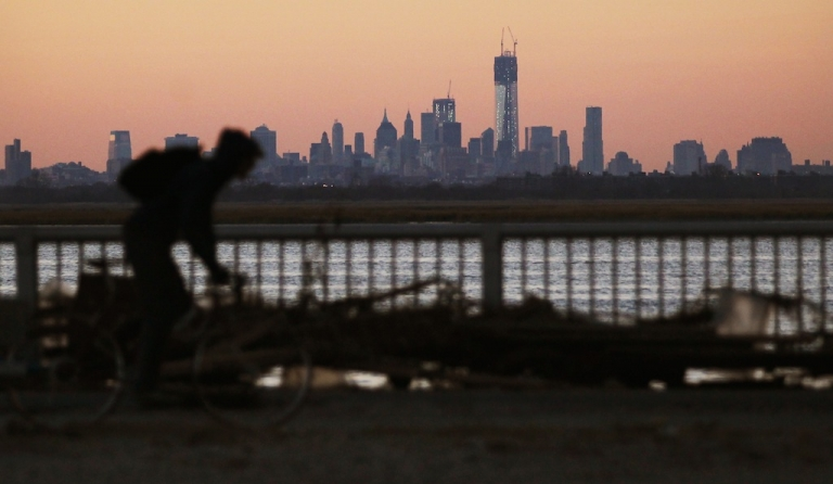 <p>A man bikes past debris in the Rockaway neighborhood with the Manhattan skyline in the distance on November 6, 2012 in the Queens borough of New York City. The Rockaway section of Queens was one of the hardest hit areas. Many voters in New York and New Jersey are voting at alternate locations in the presidential election due to disruption from Superstorm Sandy as a Nor'easter storm approaches.</p>
