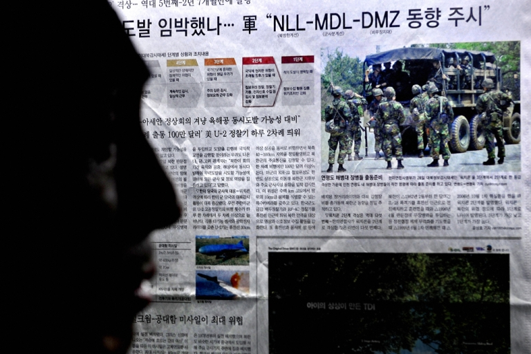 <p>A man reads a newspaper report about a North Korea missile test and the training of South Korean troops in Seoul on May 29, 2009.</p>