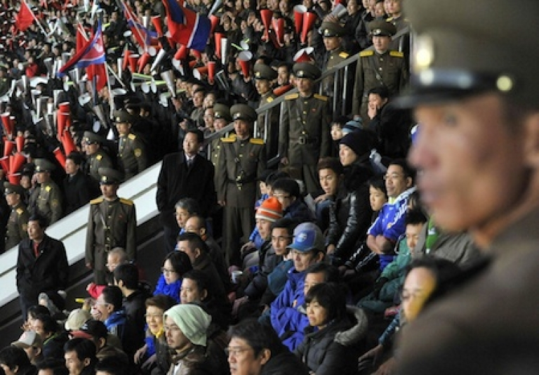 <p>North Korean security personnel stand guard around Japanese supporters (in blue), while North Korean supporters cheer for their team behind them during the World Cup 2014 qualifying match in Pyongyang on November 15, 2011. Japan was defeated by North Korea 0-1.</p>