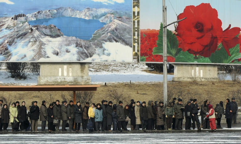 <p>North Korean commuters wait for a bus beneath posters showing Mount Paekdu and the Kim Jong-Il flower in the North Korea capital, Pyongyang.</p>