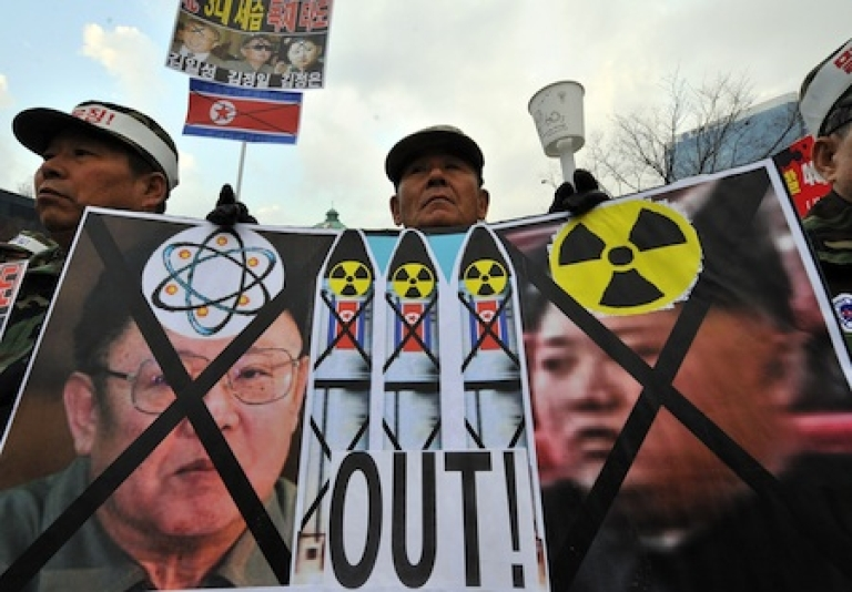 <p>A South Korean veteran holds a placard showing North Korean flags and portraits of Kim Jong-Il (L) and his son Jong-Un (R) during a rally in Seoul.</p>