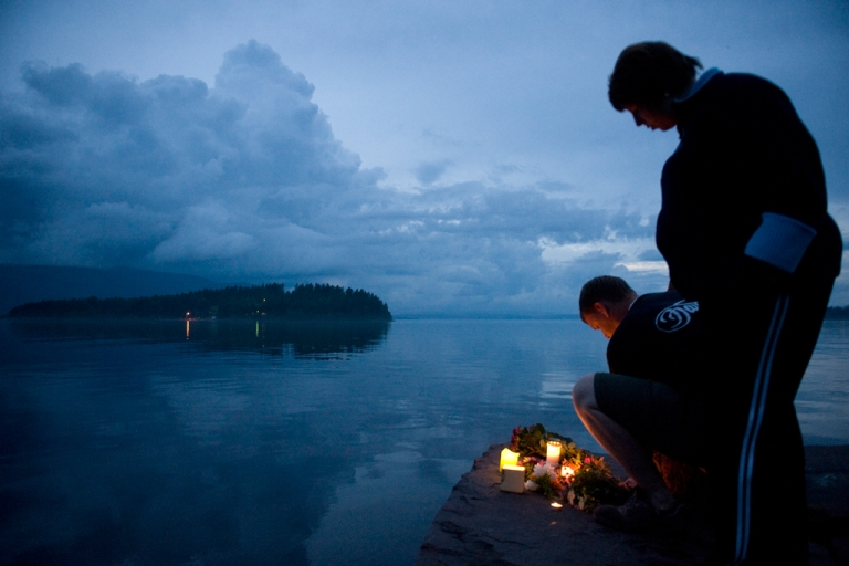 <p>The Utoeya island, 40km south west of Oslo is seen in the background as people light candles on July 23, 2011 in memory of the victims of July 22 shooting spree on the island.</p>