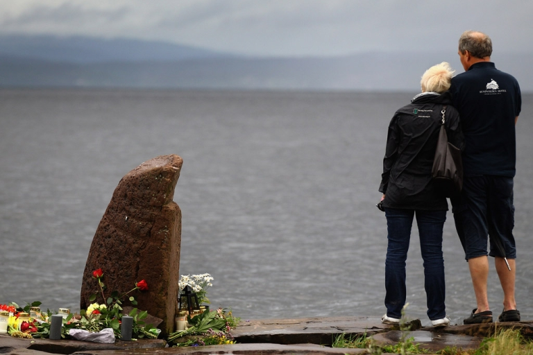 <p>A man and woman look out across Tyrifjorden Lake towards Utoya Island on July 24, 2011, in Norway. Anders Behring Breivik, 32, killed 77 people in attacks in Oslo and on the island.</p>
