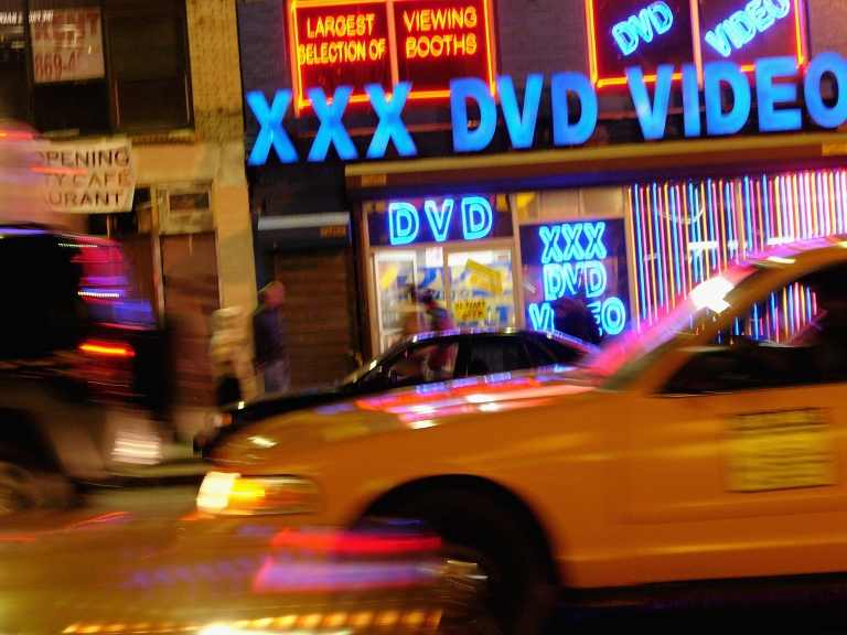 <p>Taxi cabs pass an adult video store in Times Square.</p>