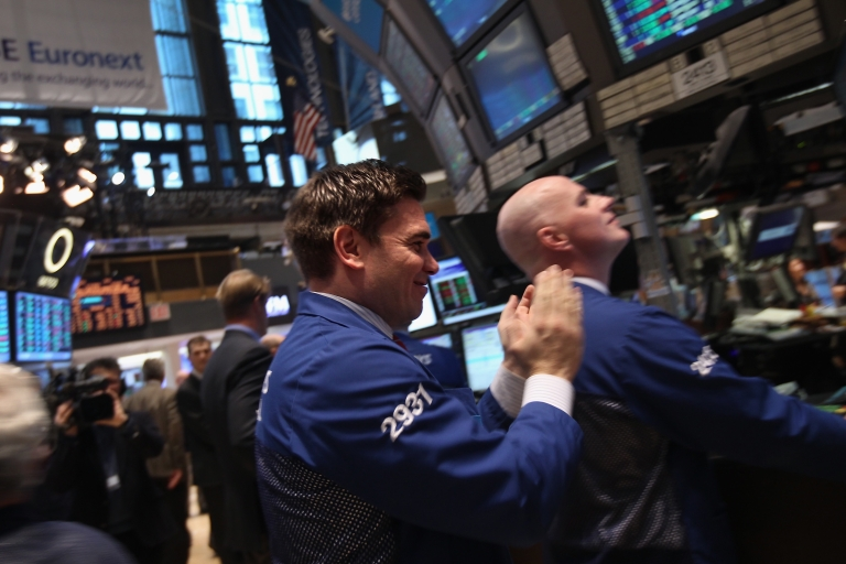 <p>A trader applauds while working on the floor of the New York Stock Exchange on Feb. 21, 2012, when the Dow Jones Industrial Average broke through the 13,000 barrier.</p>