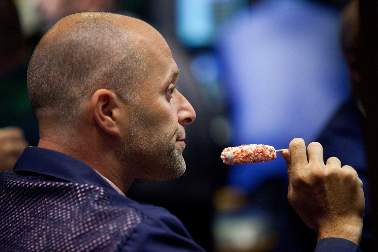 <p>A trader enjoys a frozen treat on the floor of the New York Stock Exchange in New York City on June 29, 2012.</p>