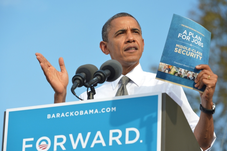 <p>US President Barack Obama shows a copy of his jobs plan as speaks during a campaign rally October 23, 2012 at Triangle Park in Dayton, Ohio.</p>