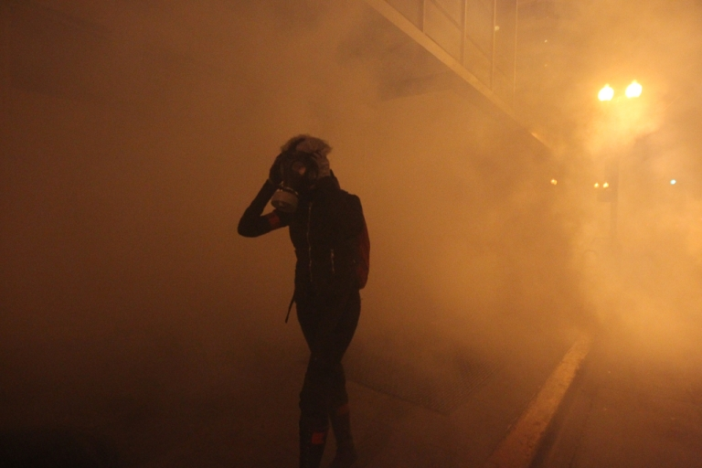 <p>A masked Occupy Wall St. demonstrator walks away as authorities deploy tear gas during an demonstration in response to an early morning police raid which displaced Occupy Oakland's tent city in Oakland, California October 25, 2011.</p>