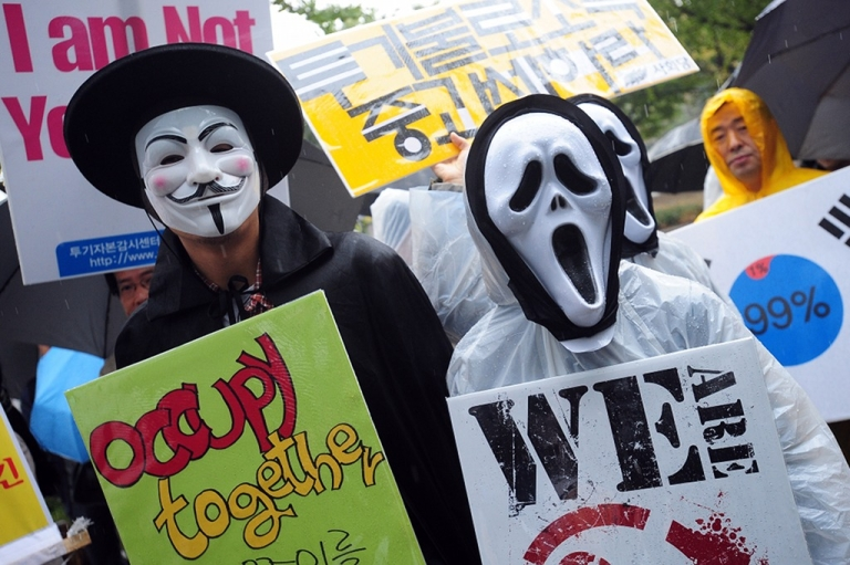 <p>South Korean protesters wearing masks hold up banners during the 'Occupy Seoul' rally as part of the worldwide protest inspired by 'Occupy Wall Street' in Seoul on October 15, 2011.</p>