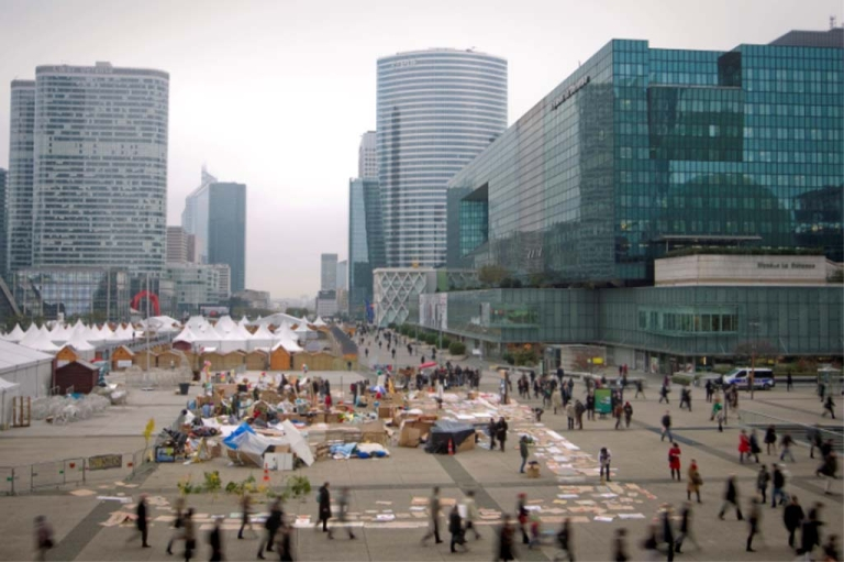 <p>Workers walk past the French 'Indignants' camp out at Paris' La Defense business district early on November 15, 2011.</p>