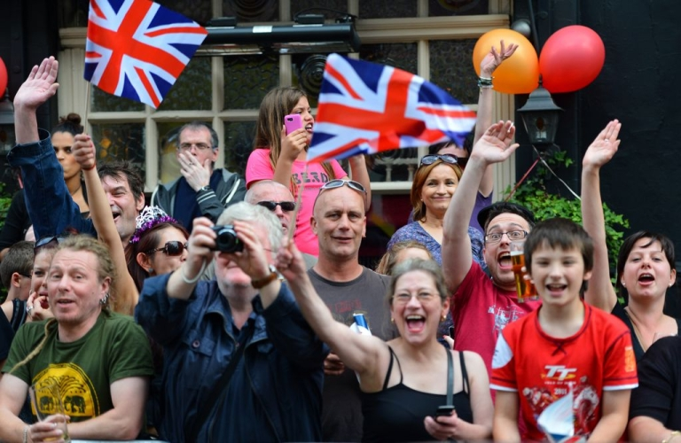 <p>Crowds cheer as the Olympic Torch passes through the streets of Hackney, north London, on July 21, 2012.</p>