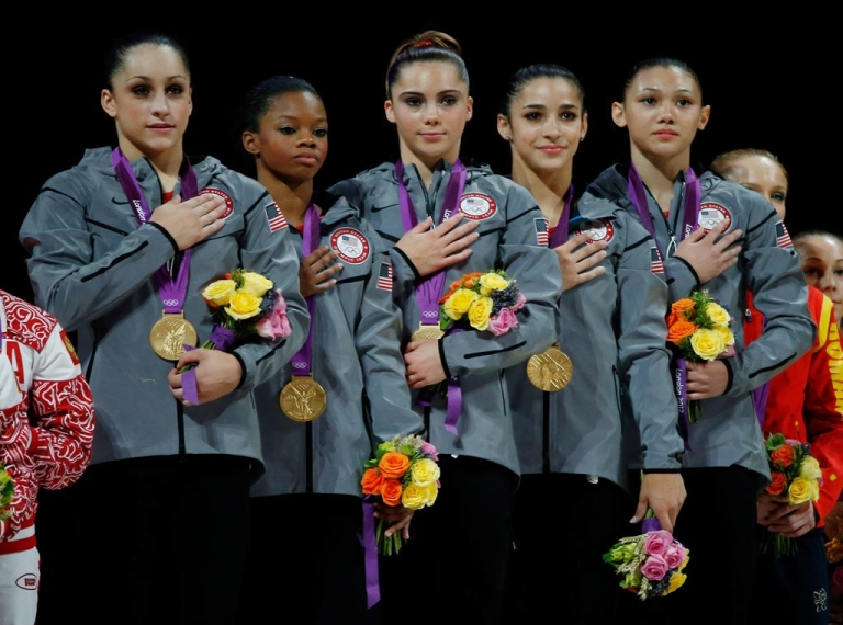 <p>Jordyn Wieber, Gabrielle Douglas, Mc Kayla Maroney, Alexandra Raisman and Kyla Ross of the United States celebrate on the podium after winning the gold medal in the Artistic Gymnastics Women's Team final on Day 4 of the London 2012 Olympic Games at North Greenwich Arena on July 31, 2012 in London, England.</p>
