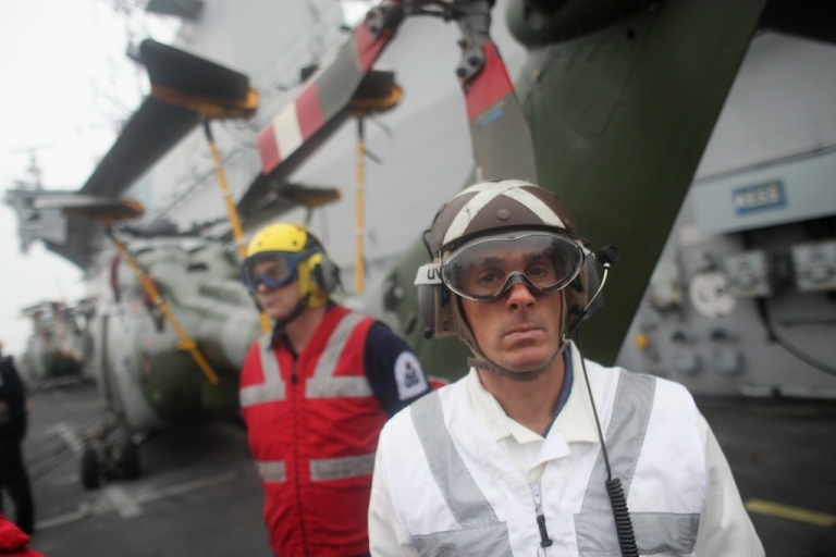 <p>Deputy Air Engineer Carl Harwood (R) aboard the Royal Navy Helicopter Carrier HMS Ocean as she makes her way up the River Thames as part of security rehearsals ahead of the London 2012 Olympics, on May 4, 2012 in London, England. The exercise is aimed at testing military capabilities to ensure operational readiness before the start of the Olympic Games.</p>