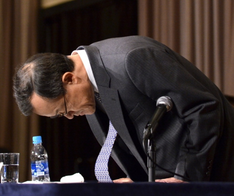 <p>Olympus president Shuichi Takayama bows in apology during a press conference to acknowledge that the company used takeover fees to hide its losses.</p>
