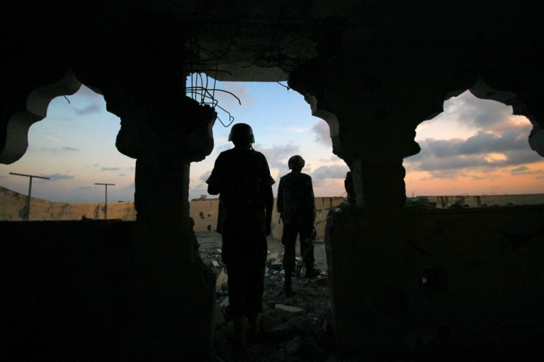 <p>Uganda soldiers serving with the African Union Mission in Somalia (Amisom) 33rd Battalion are silhouetted against the Mogadishu skyline at sundown atop a partially destroyed building in the Yaaqshiid District of Mogadishu, where Amisom forces have pushed Al Shabaab militants beyond the city's northern fringes to the outskirts of the Somalia seaside capital. This picture was taken on November 22, 2011.</p>