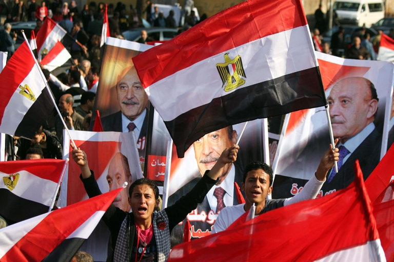 <p>Egyptian supporters hold up portraits of ex-chief of intelligence and vice president Omar Suleiman in Cairo on December 2, 2011. Suleiman announced on April 6, 2012, that he would run during Egypt's presidential elections next month.</p>