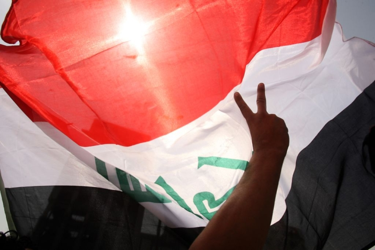 <p>An Iraqi demonstrator makes the victory sign as he waves his national flag during a weekly protest against corruption, unemployment and poor public services at Baghdad's Tahrir Square on April 29, 2011.</p>