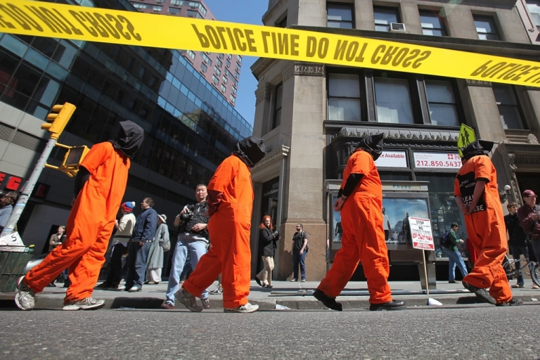<p>Protesters dressed as Guantanamo Bay prisoners march down Broadway during a large anti-war rally on April 9, 2011 in New York City.</p>
