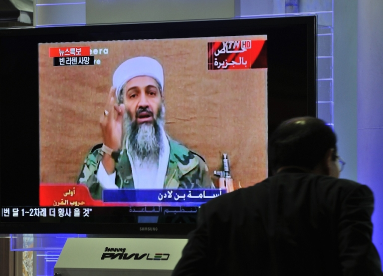 <p>A pedestrian walks past a TV news report about the killing of Osama Bin Laden, at a railway station in Seoul on May 2, 2011.</p>