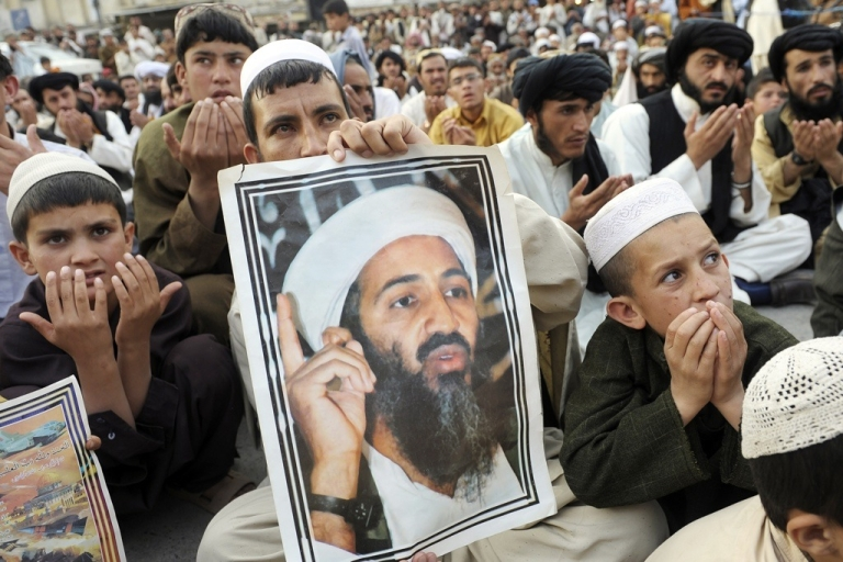 <p>Supporters of hard line pro-Taliban party Jamiat Ulema-i-Islam-Nazaryati carry portraits of slain Al Qaeda leader Osama bin Laden as they pray for bin Laden during an anti-US rally in Quetta, Pakistan on May 2, 2012, the first anniversary of the death of Osama bin Laden. Pakistan was in a state of high alert on May 2, over fears militants will launch revenge attacks on the first anniversary of Osama bin Laden's killing by American Navy SEALs.</p>