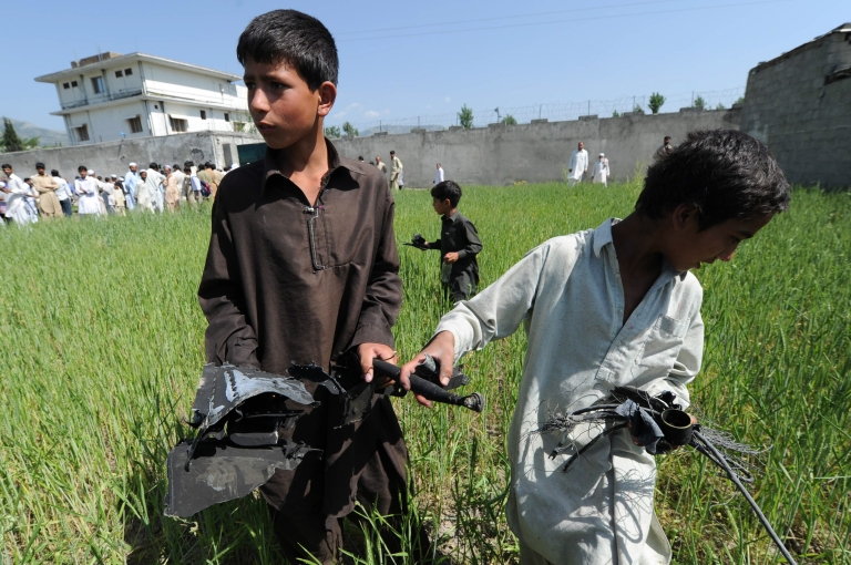 <p>Pakistani boys collect debris at the site of the crashed helicopter outside the luxury compound that hid Al Qaeda leader Osama bin Laden in Abbottabad on May 3, 2011.</p>
