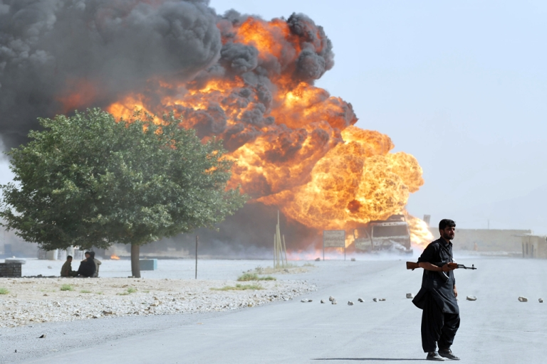 <p>A Pakistani security personnel stands guard near a burning NATO oil tanker on the outskirts of Quetta on August 3, 2011. According to an official, two NATO oil tankers carrying logistic for ISAF forces from Karachi combusted after the vehicles where intercepted by armed men and fired upon.</p>