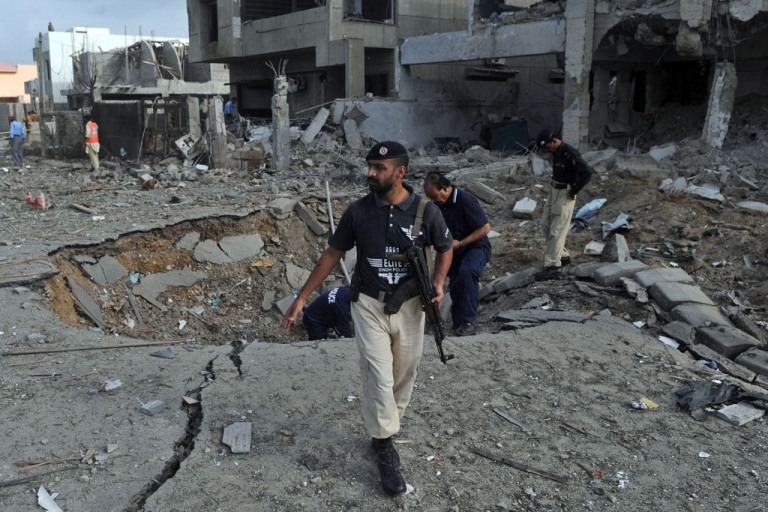 <p>Pakistani investigators inspect the crater caused by a bomb blast in Karachi on Sept. 19, 2011.</p>