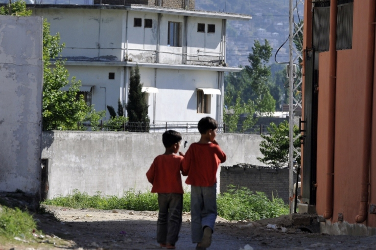 <p>Pakistani boys walk toward Osama Bin Laden's final hideout as military and police keep the area cordoned off in the Bilal Town neighborhood of Abbottabad on May 8, 2011.</p>