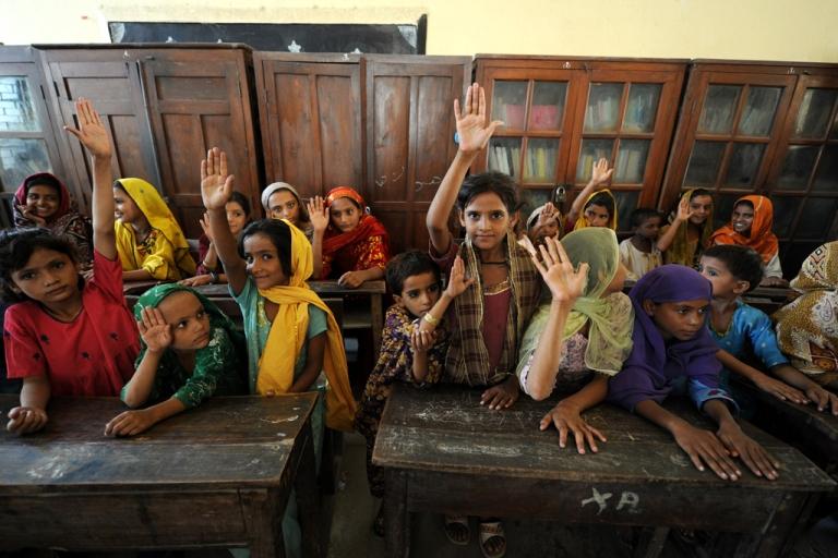 <p>Pakistani children raise their hands.</p>