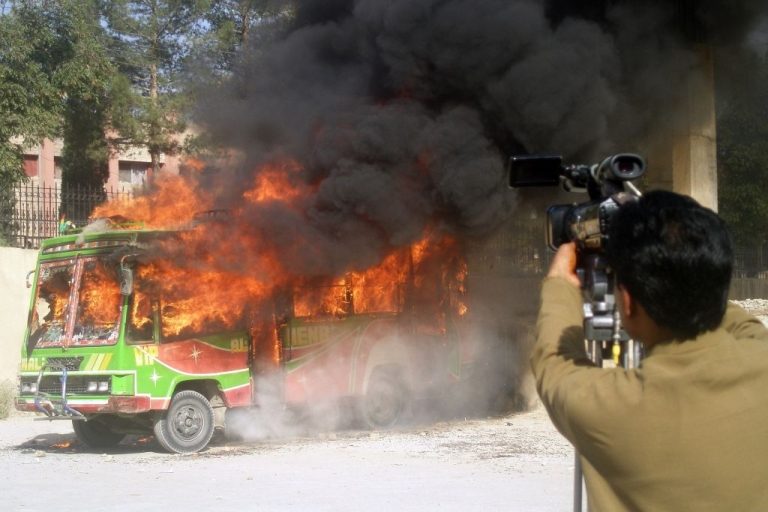 <p>Pakistani media film a bullet-riddled burning bus in Quetta on October 4, 2011. Gunman attacked a bus carrying Shiite Muslims in Pakistan's insurgency-torn southwestern province of Baluchistan on October 4, killing 13 people and injuring six others, police said.</p>