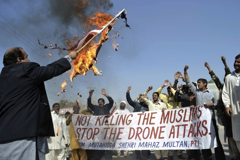 <p>A Pakistani protester holds a burning US flag as they shout slogans during a protest in Multan on February 9, 2012 against the US drone attacks in the Pakistani tribal region.</p>