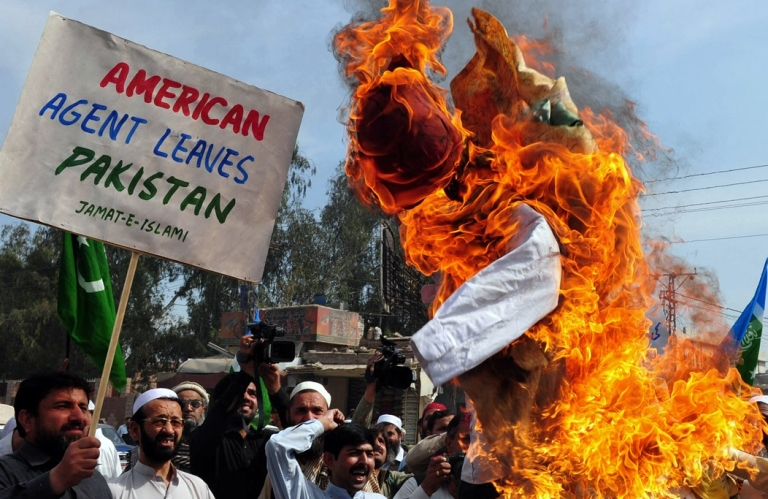 <p>Activists of the Pakistani fundamentalist Islamic party Jamaat-i-Islami (JI) shout slogans beside a burning effigy of CIA contractor Raymond Davis during a protest in Peshawar on March 18, 2011. Thousands of people took to the streets across Pakistan on March 18 to protest a US drone strike that killed 35 people.</p>