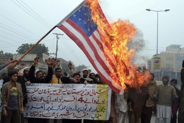 <p>Pakistani demonstrators shout slogans beside a burning US flag during a protest in Multan on January 3, 2013, against the drone attacks in Pakistan's tribal areas. Pakistani warlord Mullah Nazir, who sent men to fight NATO troops in Afghanistan, was killed in a US drone strike in Pakistan along with five loyalists, local security officials said. Experts fear drone strikes will radicalize locals and create more enemies for the US.</p>