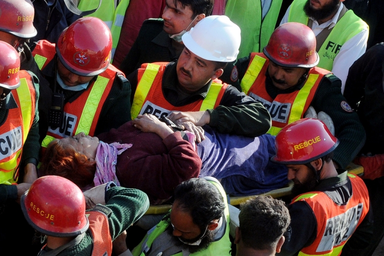 <p>Pakistani rescue workers carry an elderly survivor on a stretcher during continued search for victims from the debris of a collapsed building in Lahore on February 7, 2012. Pakistani rescuers on February 7 plucked survivors from the rubble of a collapsed factory in Lahore, where another 10 people are still buried under the debris and the death toll rose to 19. The three-storey building used to manufacture veterinary medicines caved in from a probable boiler and a gas cylinder explosion at the premises in the congested Multan Road area of Pakistan's second largest city on February 6. AFP PHOTO / ARIF ALI</p>
