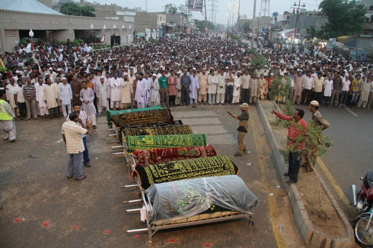 <p>Pakistani Muslims offer funeral prayers of garment factory workers who were killed after fire erupted the factory in Karachi on September 12, 2012. Pakistani police registered murder cases against the factory owners and managers on September 13, 2012.</p>