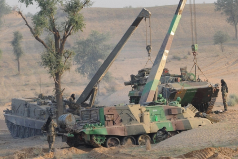 <p>An Indian Army armoured personnel carrier (R) is lifted by cranes before maneuvers during the Shoor Veer military exercise near Hanumangarh, located near the India-Pakistan border, on May 3, 2012. More than 300 combat vehicles and 60,000 troops took part in the exercise held in the Indian desert state which borders Pakistan.</p>