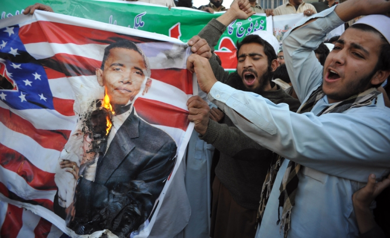 <p>Pakistani protestors burn a portrait of President Barack Obama and a US flag during a demonstration in Peshawar on November 29, 2011, held to protest a NATO strike on Pakistan troops.</p>